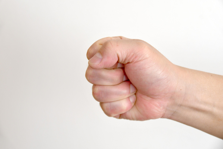 グーを出した男性の手