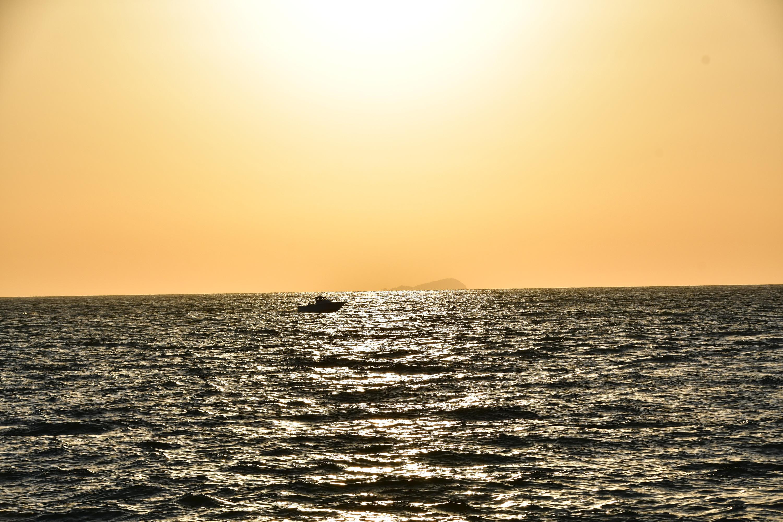 海に浮かぶ船とオレンジ色の空