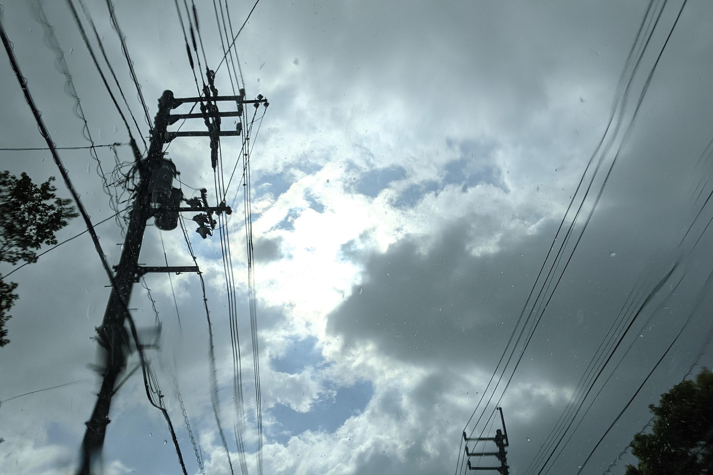 曇り空の合間から見える太陽と電柱
